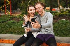 Foto dell'uomo sportivo allegro delle coppie e della donna 20s in abiti sportivi, immagini stock
