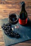 Foto della bottiglia di vino rosso, vetro di vino con vino, uva nera sul bordo di pietra Fotografia Stock Libera da Diritti