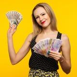 Foto della condizione felice della giovane donna isolata sopra fondo giallo Esaminando macchina fotografica che tiene soldi fotografia stock libera da diritti