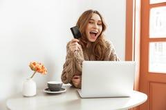 Foto della donna castana adorabile 20s in maglione che fa sho online Immagine Stock Libera da Diritti