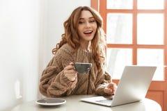 Foto della donna castana 20s in maglione con il drin marrone lungo dei capelli Immagini Stock