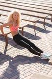 Foto della donna di sport che si esercita fra i banchi nel giorno di estate Immagini Stock