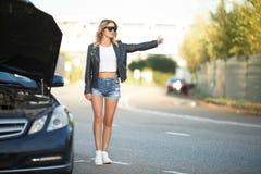 Foto della giovane donna con la condizione sollevata della mano vicino all'automobile rotta con il cappuccio aperto immagini stock libere da diritti