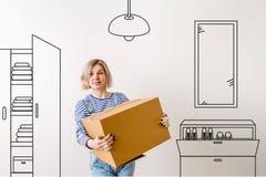 Foto della giovane donna con la scatola di cartone con dipinto sul guardaroba della parete, scarpa, specchio, Fotografie Stock Libere da Diritti