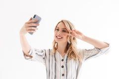 Foto della giovane donna piacevole che prende selfie mentre sorridono e mostrando la pace canti fotografia stock