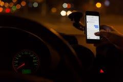 Foto della mano che scrive gli sms a macchina su uno smartphone nell'automobile Immagini Stock