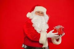 Foto della mano gloved di Santa Claus con giftbox, su un backgrou rosso immagine stock