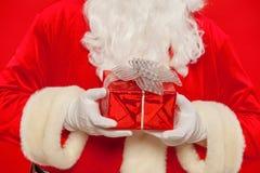 Foto della mano gloved di Santa Claus con giftbox, su un backgrou rosso fotografia stock libera da diritti