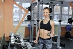 Foto della ragazza atletica che fa un allenamento di forma fisica con le teste di legno nella palestra Fotografia Stock Libera da Diritti