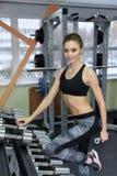 Foto della ragazza atletica che fa un allenamento di forma fisica con le teste di legno nella palestra Fotografie Stock Libere da Diritti