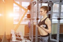 Foto della ragazza atletica che fa un allenamento di forma fisica con le teste di legno nella palestra Fotografie Stock