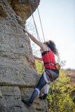 Foto della ragazza dell'atleta che scala sopra la roccia fotografie stock