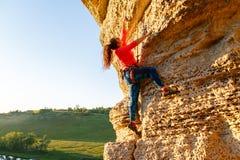 Foto della roccia rampicante della ragazza riccio-dai capelli dello scalatore Fotografie Stock