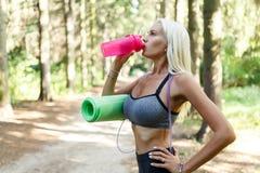 Foto della sportiva che beve dalla bottiglia rosa Fotografia Stock Libera da Diritti