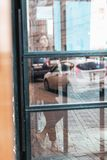 Foto della via di una ragazza con i dreadlocks dietro una porta di vetro immagine stock libera da diritti