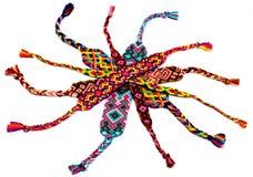 Foto delle bagattelle colorate dei braccialetti intrecciate dai fili Fotografia Stock