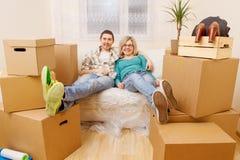 Foto delle coppie che si siedono sullo strato fra le scatole di cartone Immagini Stock Libere da Diritti