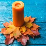 Foto delle foglie arancio di autunno e della candela Immagine Stock
