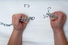Foto delle mani che tengono una catena rotta fotografia stock