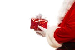 Foto delle mani gloved di Santa Claus che tengono giftbox rosso, isolata sul Natale bianco del fondo immagini stock