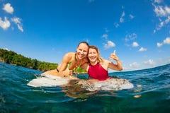 Foto delle ragazze felici del surfista che si siedono sui bordi di spuma fotografia stock libera da diritti