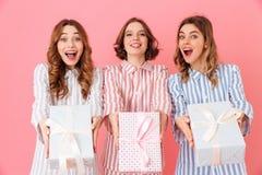 Foto delle ragazze felici 20s nella tenuta e nella dimostrazione di usura di svago Fotografia Stock