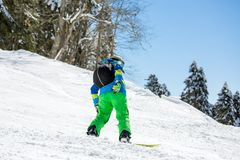 Foto dello snowboard di guida dell'uomo dalla collina nevosa Fotografia Stock Libera da Diritti