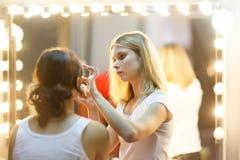 Foto dello stilista con la ragazza davanti allo specchio con le luci immagini stock libere da diritti