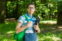 Foto dello studente con la matita in bocca, vetri Immagini Stock