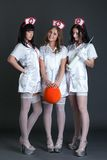 Foto dello studio delle ragazze vestite come infermieri sexy Immagini Stock Libere da Diritti