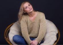 Foto den härliga flickan i en stol Fotografering för Bildbyråer