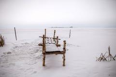 Foto der Bank gemacht von den Birkenklotz, schneebedecktes Feld Stockfoto