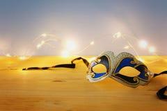 Foto der eleganten venetianischer, Karnevalmaske über Holztisch und der Girlandengoldlichter stockfotografie
