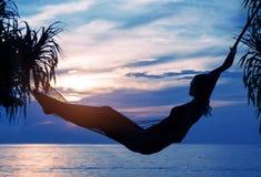 Foto der entspannten Frau stillstehend und den Sonnenaufgang betrachtend stockfoto