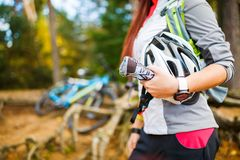 Foto der Frau mit dem Sturzhelm, der gegen Hintergrund des Fahrrades steht Lizenzfreie Stockfotografie