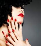 Foto der Frau mit den roten Nägeln und Lippen der Mode Stockfotografie