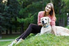 Foto der Frau und des Hundes, die auf Rasen sitzen Lizenzfreie Stockbilder