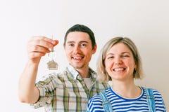 Foto der Frau und des Mannes mit Schlüsseln von der Wohnung gegen leere Wand Lizenzfreies Stockfoto