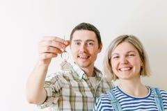 Foto der Frau und des Mannes mit Schlüsseln von der Wohnung gegen leere Wand Stockfoto
