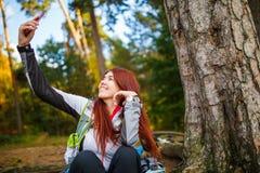 Foto der glücklichen Frau im herbstlichen Wald fotografierend Lizenzfreie Stockbilder