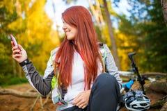 Foto der glücklichen Frau mit Handy im Herbstwald Lizenzfreie Stockfotos