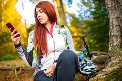 Foto der glücklichen Frau mit Handy im Herbstwald Stockbild