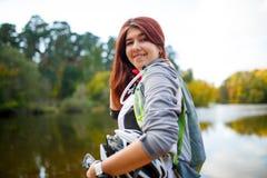 Foto der glücklichen Frau mit Rucksack- und Fahrradsturzhelm Lizenzfreies Stockbild