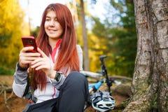 Foto der glücklichen Frau mit Smartphone im Herbstwald Stockbilder