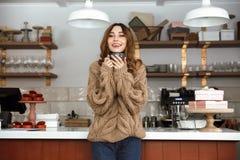 Foto der glücklichen Frau in der Strickjacke, die nahe Buffet im Café steht und stockfotografie
