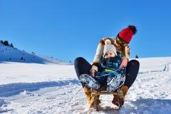 Foto der glücklichen Mutter und des Kindes, die im Schnee mit einem Schlitten an einem sonnigen Wintertag spielt Stockbild