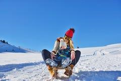 Foto der glücklichen Mutter und des Kindes, die im Schnee mit einem Schlitten an einem sonnigen Wintertag spielt Lizenzfreie Stockbilder