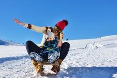 Foto der glücklichen Mutter und des Kindes, die im Schnee mit einem Schlitten an einem sonnigen Wintertag spielt Lizenzfreie Stockfotografie