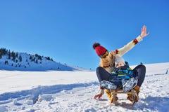 Foto der glücklichen Mutter und des Kindes, die im Schnee mit einem Schlitten an einem sonnigen Wintertag spielt Stockbilder