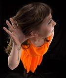 Foto der hörenden Frau im orange Kleid lizenzfreie stockfotografie